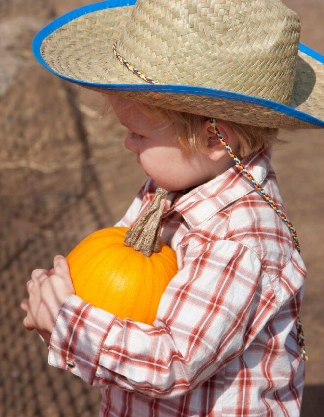 boy in cowboy hat holds pumpkin